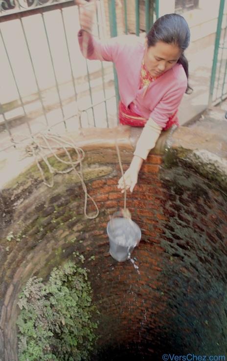 femme puisant eau puit nepal